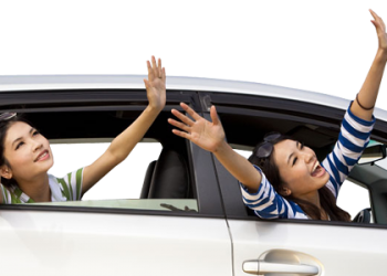 Happy Woman Raising Hand Out Of Car Window