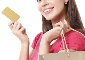 Happy young woman holding shopping bags and visa credit card